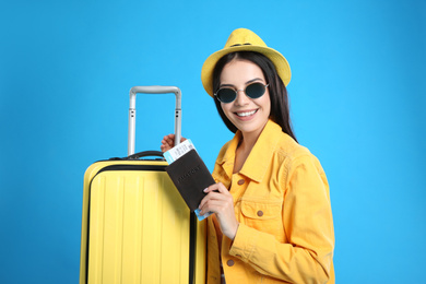 Beautiful woman with suitcase and ticket in passport for summer trip on blue background. Vacation travel