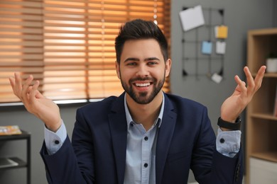 Happy young businessman conducting webinar in office