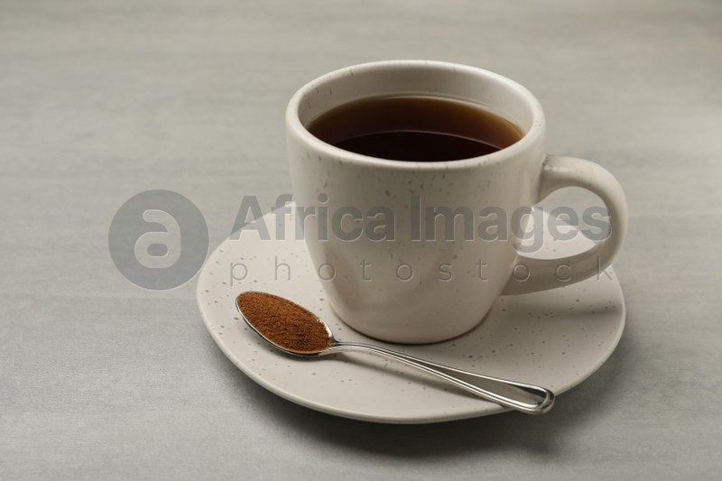 Cup of delicious chicory drink and spoon with powder on light grey table