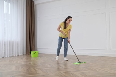 Young woman cleaning floor with mop in empty room