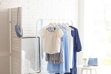 Wardrobe rack with women's clothes at white brick wall in room