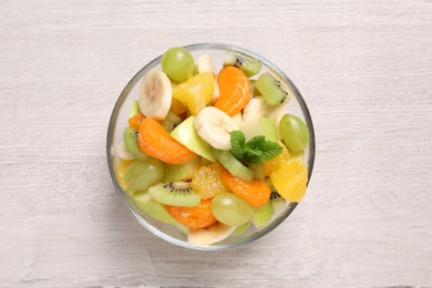 Delicious fresh fruit salad in bowl on white wooden table, top view