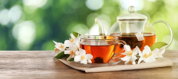 Jasmine tea and fresh flowers on wooden table outdoors, space for text. Banner design
