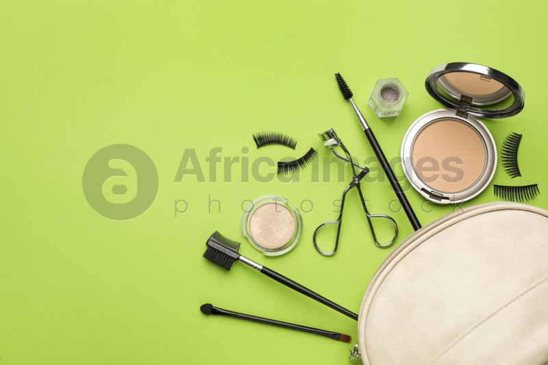 Flat lay composition with eyelash curler, makeup products and accessories on light green background. Space for text