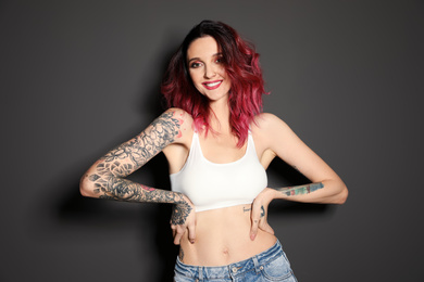 Beautiful woman with tattoos on body against black background
