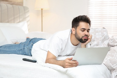 Lazy young man with laptop on bed at home
