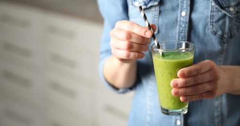 Woman with delicious kiwi smoothie indoors, closeup. Space for text