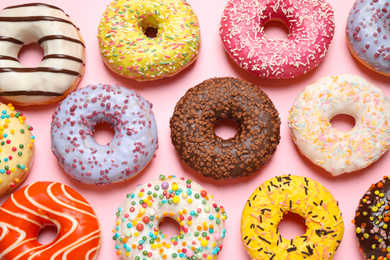 Delicious glazed donuts on pink background, flat lay