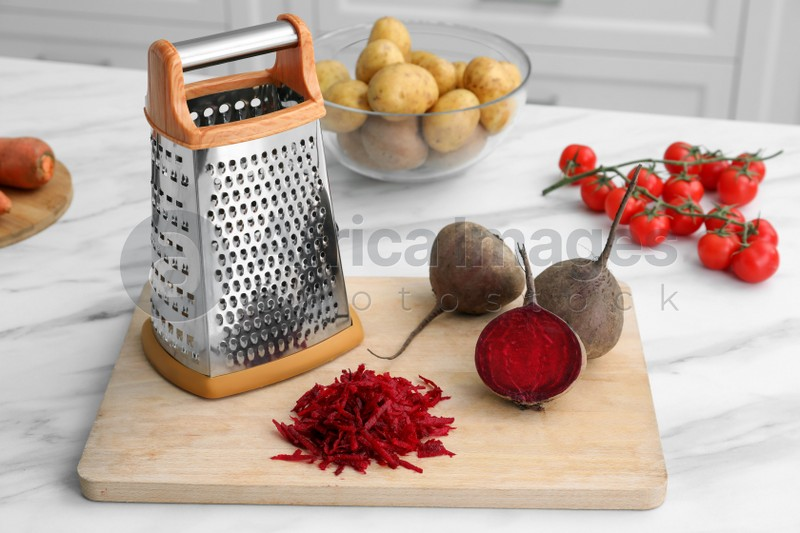 Grater and fresh ripe beetroots on white marble table