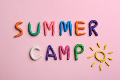 Phrase SUMMER CAMP made of colorful clay on pink background, flat lay