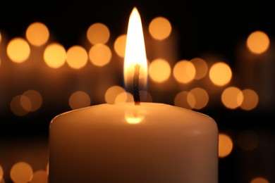 Burning candle in darkness, closeup. Memory day