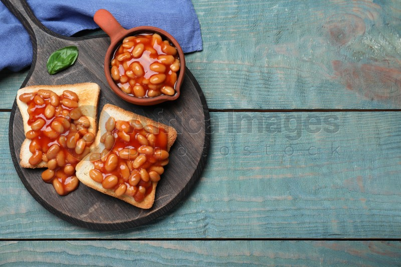 Toasts with delicious canned beans on light blue wooden table, top view. Space for text