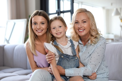 Young woman with mature mother and little daughter in living room