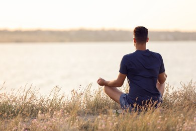 Man meditating near river on sunny day, back view. Space for text