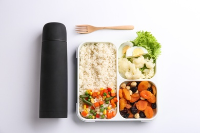 Thermos and lunch box with food on white background, top view