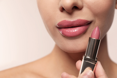 Woman with pink lipstick on light background, closeup