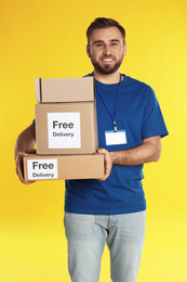 Male courier holding parcels with stickers Free Delivery on yellow background
