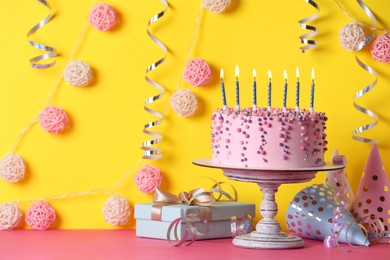 Delicious birthday cake and party decor on pink table against yellow background
