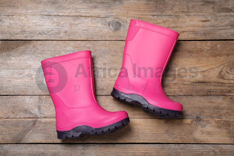 Pair of bright pink rubber boots on wooden background, top view