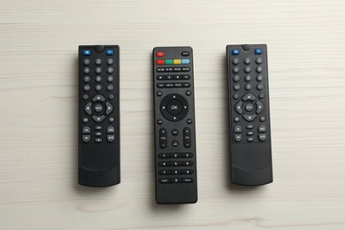 Modern tv remote controls on white wooden table, flat lay