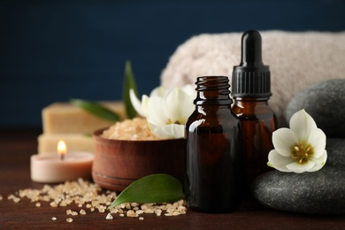 Closeup composition with skin care products, aroma oil and spa stones on wooden table. Space for text
