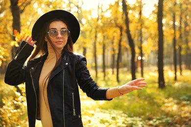 Beautiful happy woman walking in park on autumn day