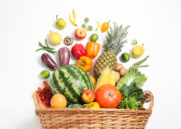 Basket with assortment of fresh organic fruits and vegetables on white background, top view