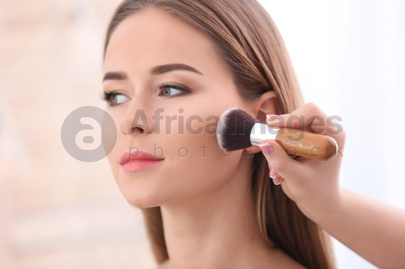 Professional visage artist applying makeup on woman's face in salon, closeup