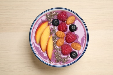 Delicious acai smoothie with fruits and almonds in bowl on wooden table, top view