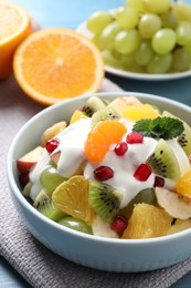 Delicious fruit salad with yogurt on table, closeup