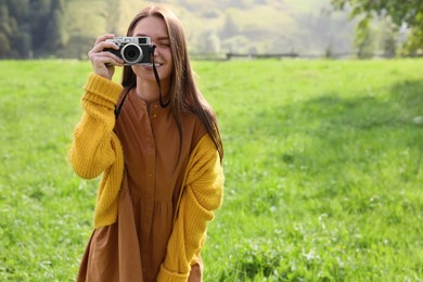 Woman taking photo with camera on green meadow