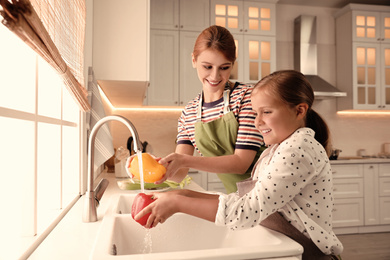 Mother and daughter washing vegetables in kitchen