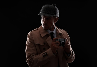 Old fashioned detective with camera on dark background