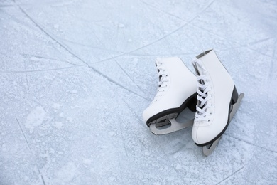 Figure skates with laces on ice, space for text. Winter outdoor activities