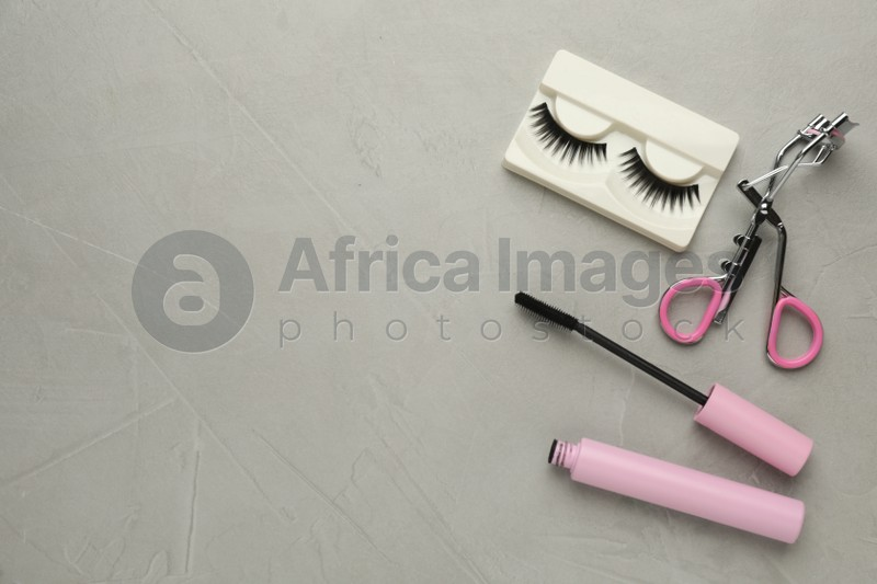 False eyelashes, curler and mascara on grey table, flat lay. Space for text