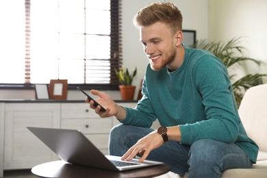 Young man using smartphone and laptop in living room