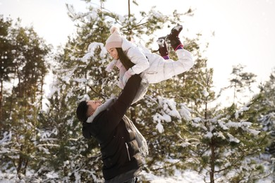 Happy father and daughter playing outdoors on winter day. Christmas vacation
