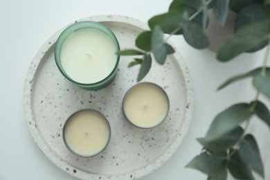 Candles and eucalyptus branches on white table, flat lay. Interior element