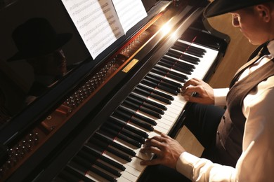Man playing piano indoors, above view. Talented musician