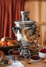 Traditional Russian samovar and treats on wooden table