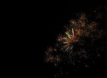 Beautiful bright fireworks lighting up night sky, space for text