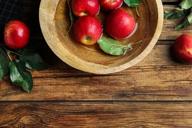 Ripe red apples in bowl of water on wooden table, flat lay. Space for text