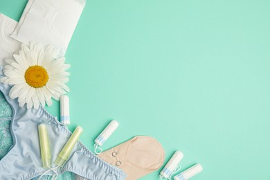 Tampons and other menstrual hygienic products on turquoise background, flat lay. Space for text