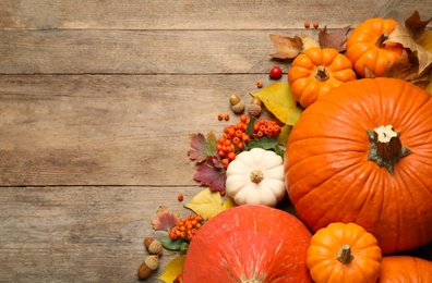Flat lay composition with pumpkins and autumn leaves on wooden table. Space for text