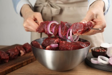 Woman stringing marinated meat on skewer at wooden table, closeup