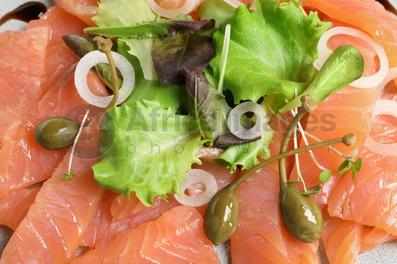 Delicious salmon carpaccio with capers on plate, top view