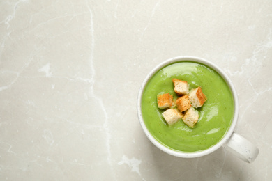 Tasty homemade zucchini cream soup on light table, top view. Space for text