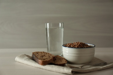 Buckwheat porridge, bread and glass of water on white wooden table. Fasting meals for Lent season