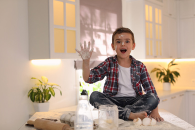 Emotional little boy with flour on face in kitchen. Cooking dough