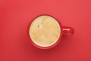 Cup of aromatic coffee on red background, top view